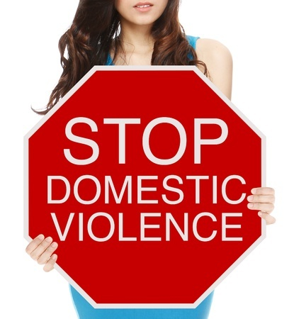 a woman holding a conceptual stop sign on domestic abuse or violence