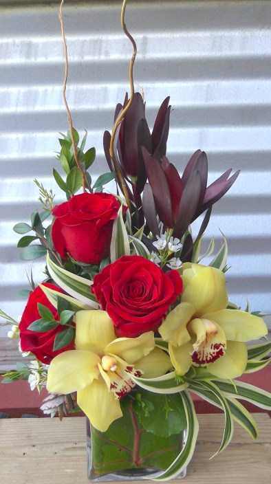 $54 Red rose trio pairs with exotic cimbidium orchids in leaf lined glass cube. Approx size 20x9""