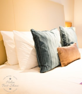 Bed piled high with soft cushions at the Amba Hotel Charing Cross