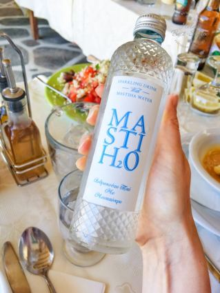 A bottle of sparkling mastic water with a white label wtih blue writing. Held above a table of food