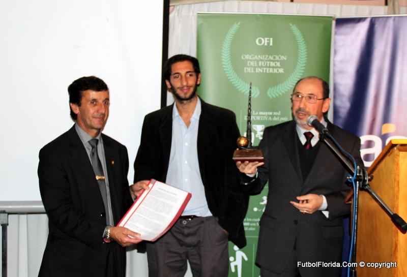 Dr Etchandy muestra el Premio Delbono junto al Presidente ares. Al centro, el hijo del Dr Ariel Delbono