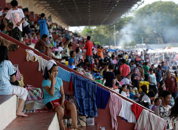 Thousands of people were camped out at a stadium Saturday to flee the fighting between government forces and Muslim rebels in Zamboanga in the Philippines. (Bullit Marquez/Associated Press)