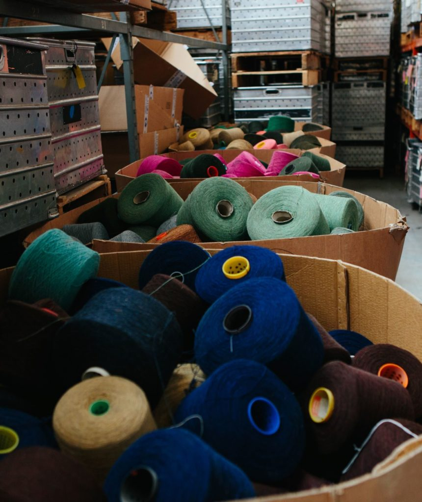 Boxes of yarn rolls in different colours in the Abraham Moon & Sons mill