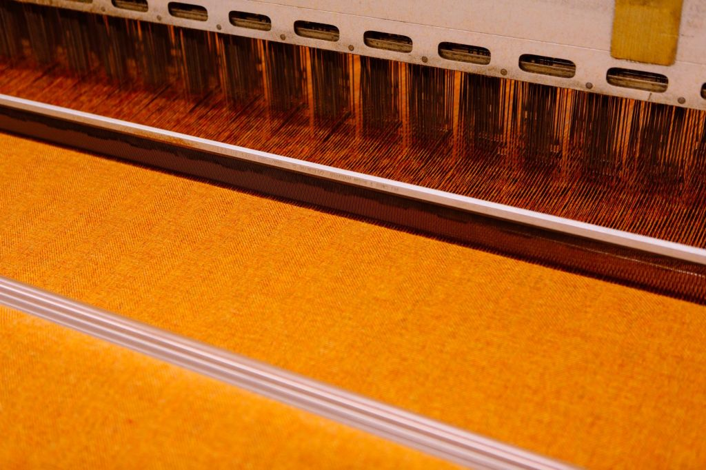 Yellow fabric being woven on a loom
