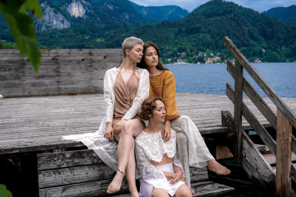Models in Josefin Wanner designs sit beside a lake
