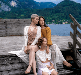 Models in Josefin Wanner designs sit beside a lake
