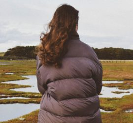 A model in dark puffa-style jacket looking over freshwater in a field