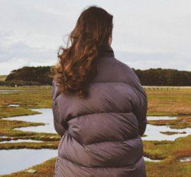 A model in dark puffa-style jacket looking over freshwater in a field