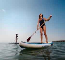 Models wearing RubyMoon navy swimsuits standing on paddleboards at sea