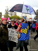 """Wonder Woman protesting with umbrella that is painted with a flower and """"They tried to bury us they didn't know we are seeds"""""""