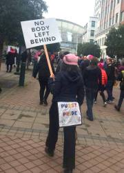 "back of protestor with booty flap reading ""Pussy Power"" and a sign for disability rights: No Body Left Behind"