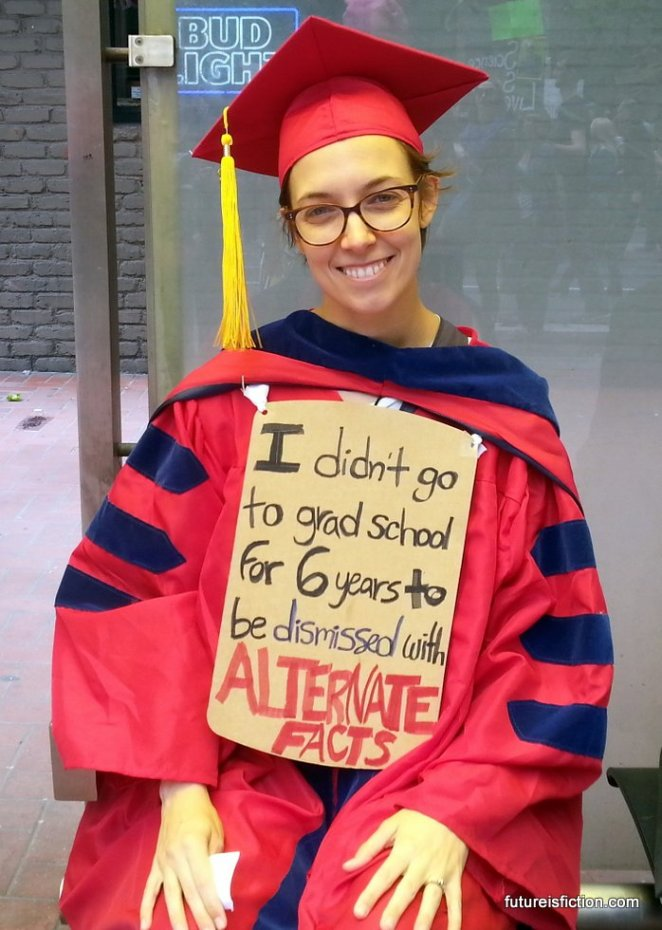 Woman in cap and gown with sign: I didn't go to school for six years to be dismissed with alternative facts