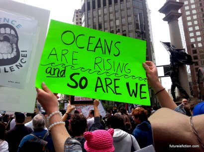 """""""Oceans are rising and so are we"""" protest sign"""