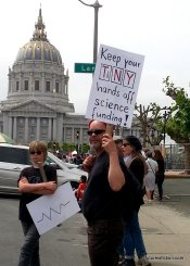 """A protest sign with """"Keep your TiNY hands off science funding!"""" where TiNY are elements from the periodic table."""