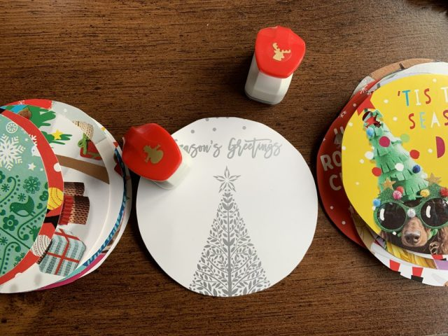 A selection of round Christmas card gift tags, on a table top, with snowman hole punch to create holes.