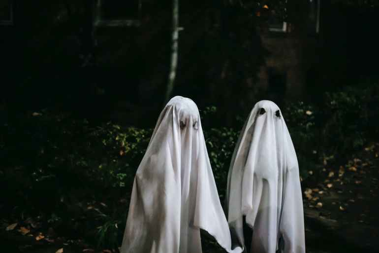 unrecognizable children in ghost costumes in town