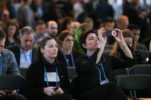 Audience snaps a photo during a talk