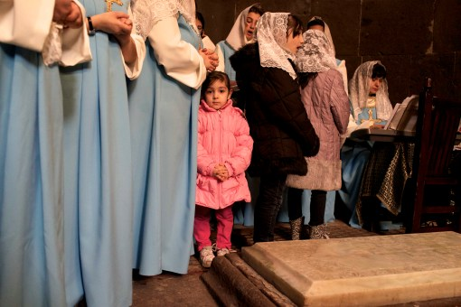 A little girl in a puffy, pink coat meets the eye of the viewer as she stands among a group of women. The women in the foreground wear long blue dresses with white sleeves and their hands are clasped. In the background another girl sits in front of a piano playing music. The group is clustered around a grave.