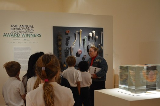 FWMoA Docent Joan Bovee leads a group of schoolchildren through a glass display at FWMoA.
