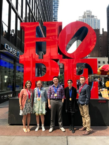 National Award recipients stand in front of Robert Indiana's HOPE sculpture in New York.
