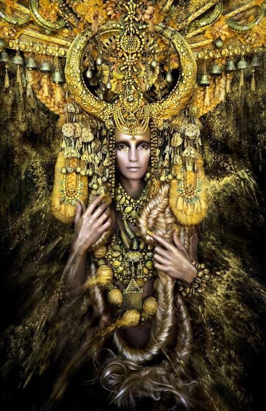 The photo is a portrait of Gaia. Her ornate headpiece takes up the majority of the top of the composition, in pieces of gold. Her long, golden hair extends around her and is clasped in her hands.