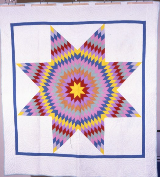 The Lone Star quilt pattern is made up of a star with a 8 points. This quilt features multiple colors.