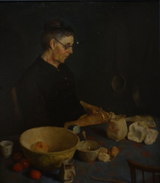 Against a dark background a woman with glasses, wearing a black dress, sits in her kitchen. She is surrounded by bowls, fruit, bread, and an urn.