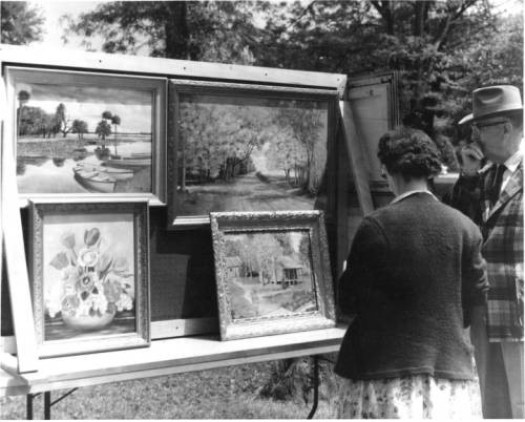 A black and white photo shows a woman and man inspecting various artworks at the Fine Arts Festival.