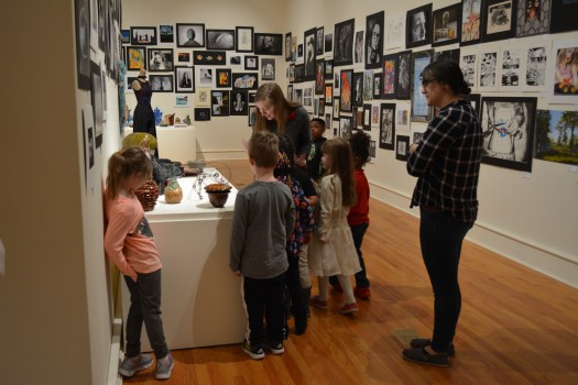 Students gather around their tour guide in the exhibition of student work to look at the ceramic sculptures.