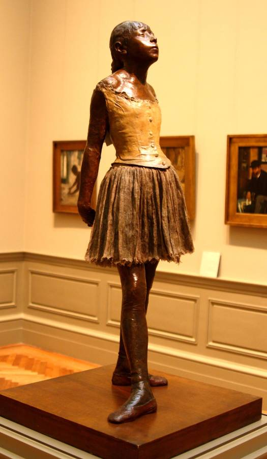A photo of the statue of a young ballerina, her hands behind her back in corset and loose skirt. Her hair is in a braid against her back and her face is upturned toward the light.