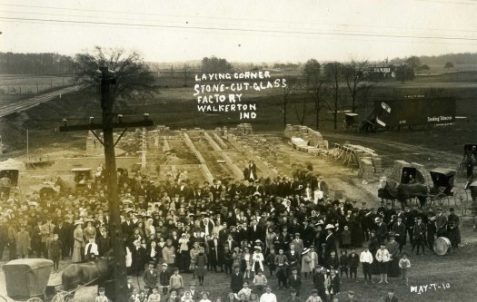 A photo showing the Walkerton, Indiana glass plant includes a crowd of people and horse-drawn carriages.