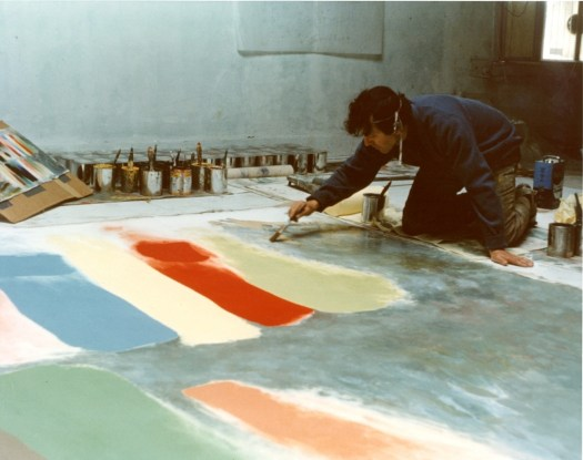 Friedel Dzubas painting. His work is on the floor, and he leans over it with a paintbrush.