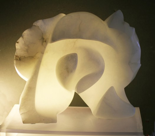 A lit, abstract sculpture made of alabaster.