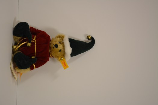 This bear is dressed for Christmas as an elf, complete with pointed hat and bells.