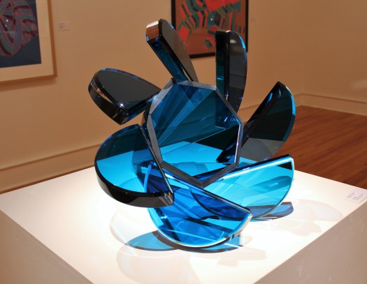 An abstract, blue glass sculpture. It is flower-like with its central circle and seven petal-like protrusions.