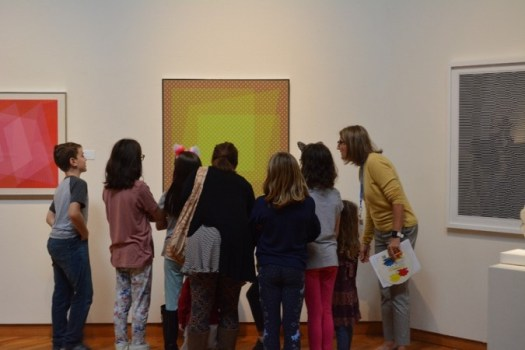 A group of school children stand in front of a painting, led in discussion by their docent.