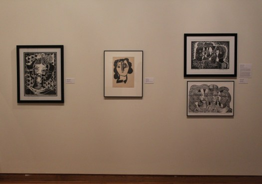 Margaret Burroughs' portrait prints hang next to a Picasso portrait print. The paper of the Picasso print has yellowed due to time, while the Burroughs' print paper remains a bright white thanks to the care of curators.