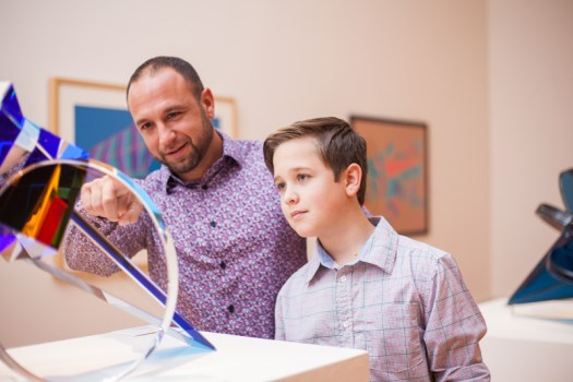 A father and son look at a glass piece on display at the museum together.