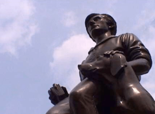Manship's bronze sculpture shows former President Abraham Lincoln as a young boy, with a dog sitting next to him, Lincoln's hand on its head. He holds a book, with his finger marking his place, in the other hand.