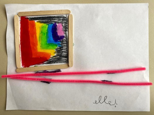 A paint stick rainbow is in the top left corner, framed with four popsicle sticks. Two pipe cleaners align the bottom of the piece of paper, one on top of the other. The artist has signed the work in the bottom right corner: Elle.