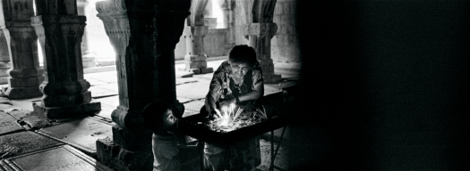 In this black and white photo, a grandmother with her grandchildren light candles in the monastery. The arches behind them cast shadows of light and dark, sparking the light of the candles to glow brightly.
