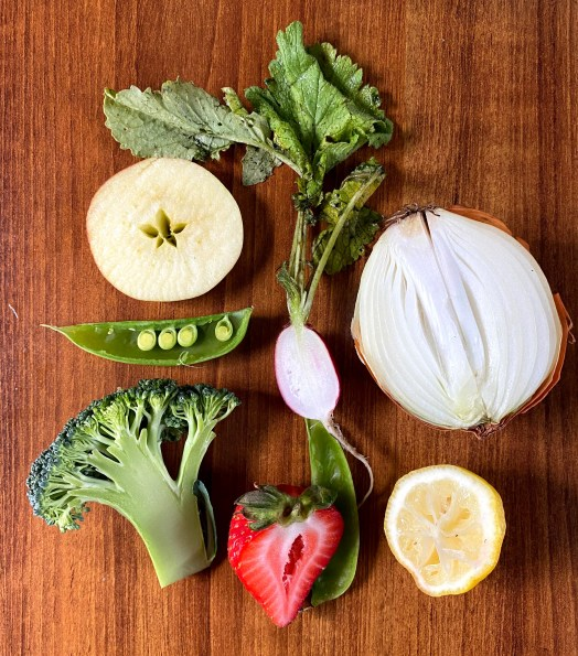 The author gathered produce from around her kitchen including: a lemon, strawberry, pea pod, onion, apple, and broccoli and then cut them in half.
