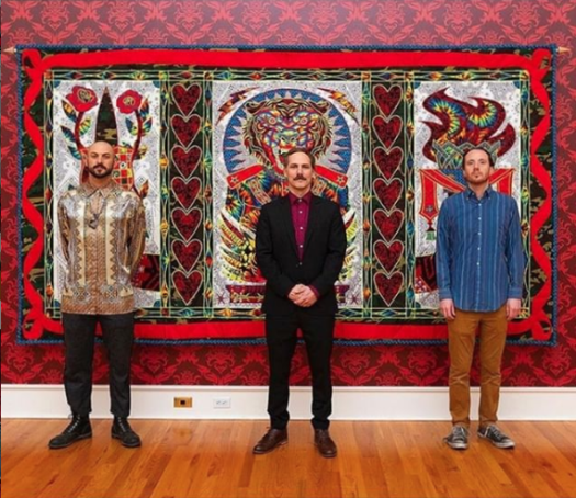 Three male artists (left to right) Lucien Shapiro, Ben Venom, and Ravi Zupa stand in front of one of Ben Venom's quilts at an exhibition at FWMoA.