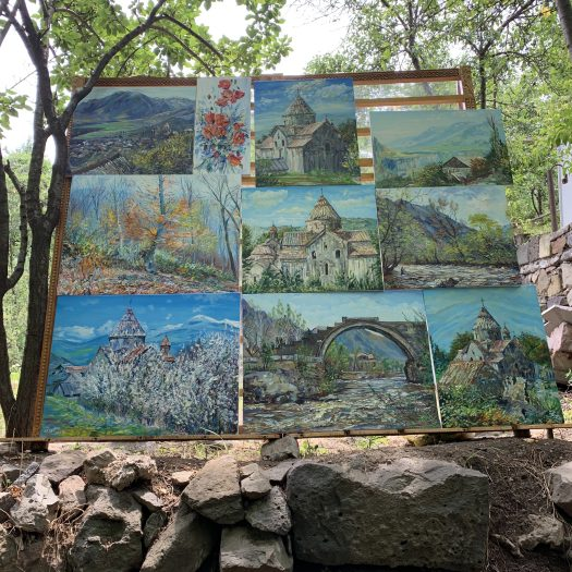 Paintings rest on a board outside Sanahin. They depict various landscapes, churches, and bridges found in the area.