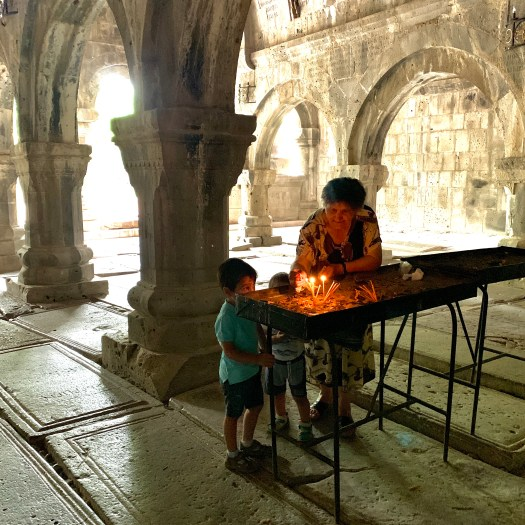 A grandmother and her grandsons light candles in an old church in Armenia.