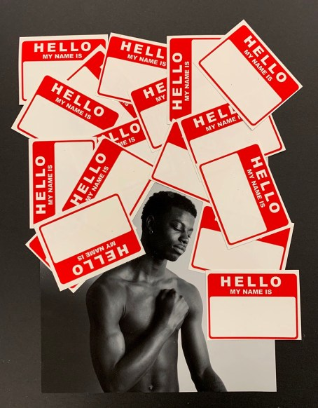 "A Black man stands without a shirt, his hand raised in a loose fist and pressing against his heart, eyes closed. Around him are multiple ""Hello My Names Is"" stickers."