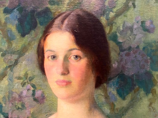 The pale, blushed face of a woman looks at the viewer. Her brown hair, parted down the middle, is pulled back. Her cheeks and lips are a pale pink. Behind her, decorative floral wallpaper with purple flowers and a green background.