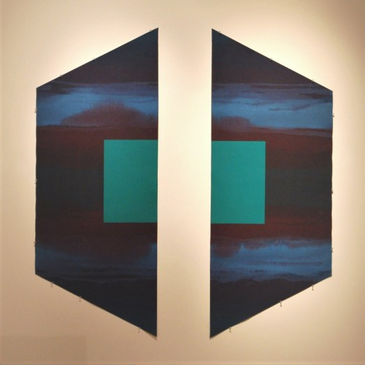 An abstract works that is cut in half, to show two symmetrical sides. The trapezoidal shape is turned on its side, with a aqua blue square halved in the center.