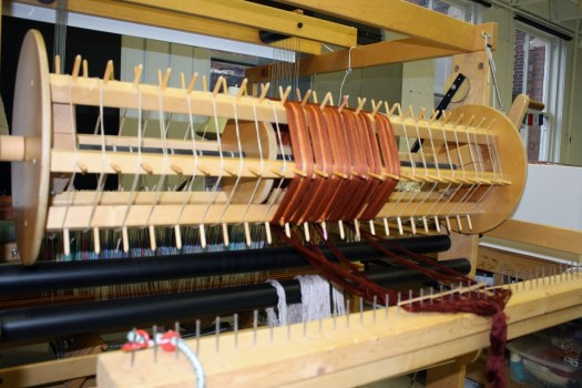 A set of measured threads are loaded onto the back of the loom.
