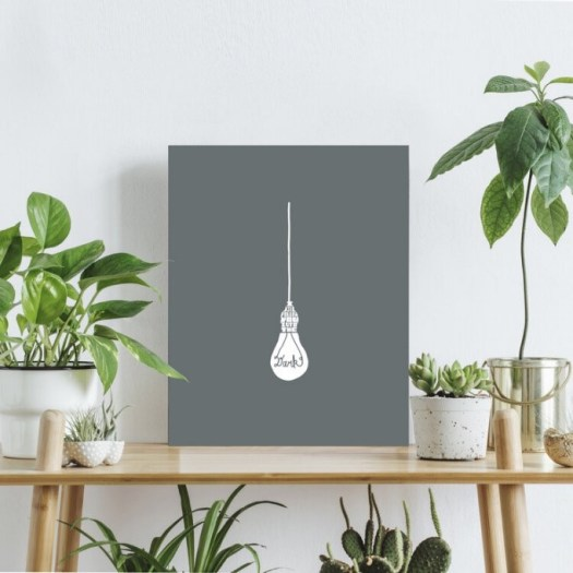 A grey print of a lightbulb hanging from a string with lyrics from the band Death Cab for Cutie.